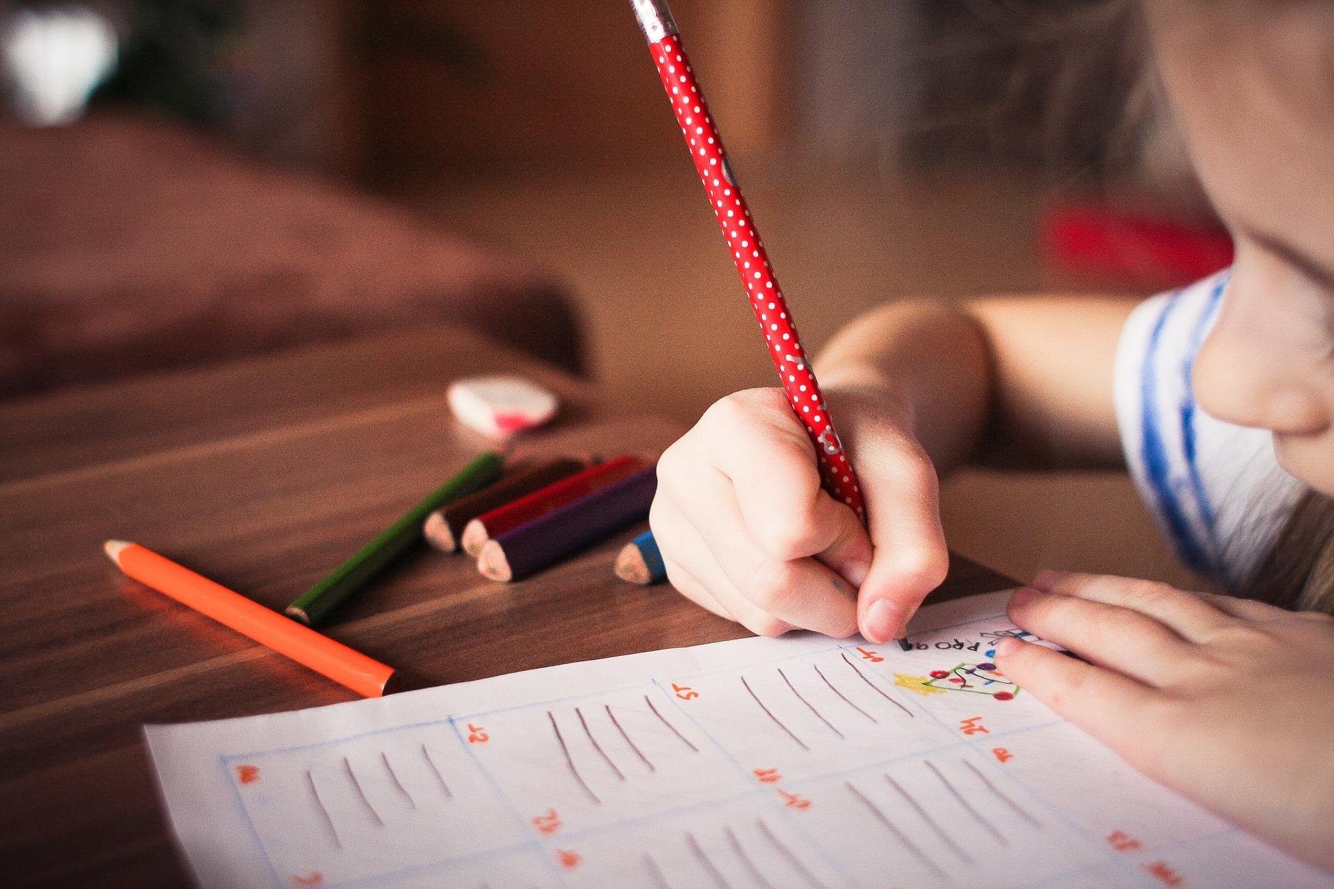 ילדה יושבת ליד שולחן ולומדת